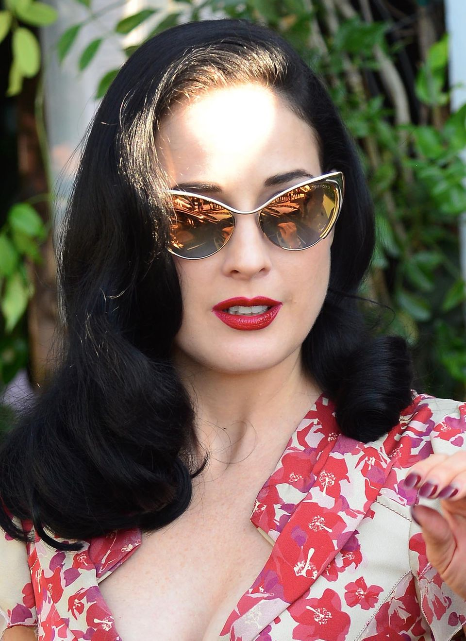 Sonnenbrillen in Katzenaugen-Form sind derzeit schwer angesagt. Dita von Teese trägt ihre voll verspiegelt und farblich passend zum Kleid.