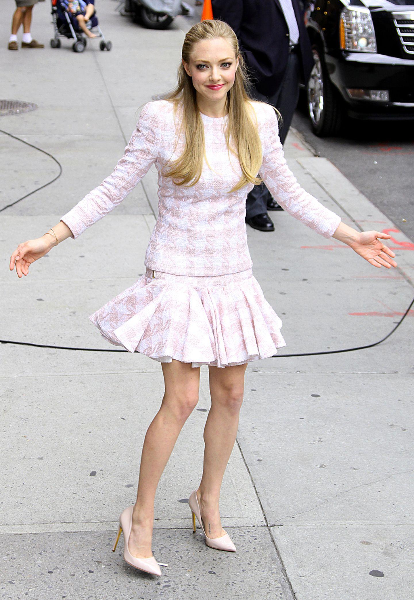 Fast wie eine Ballerina sieht Amanda Seyfried im Balmain-Dress mit rosa-weißem Hahnentrittmuster aus.
