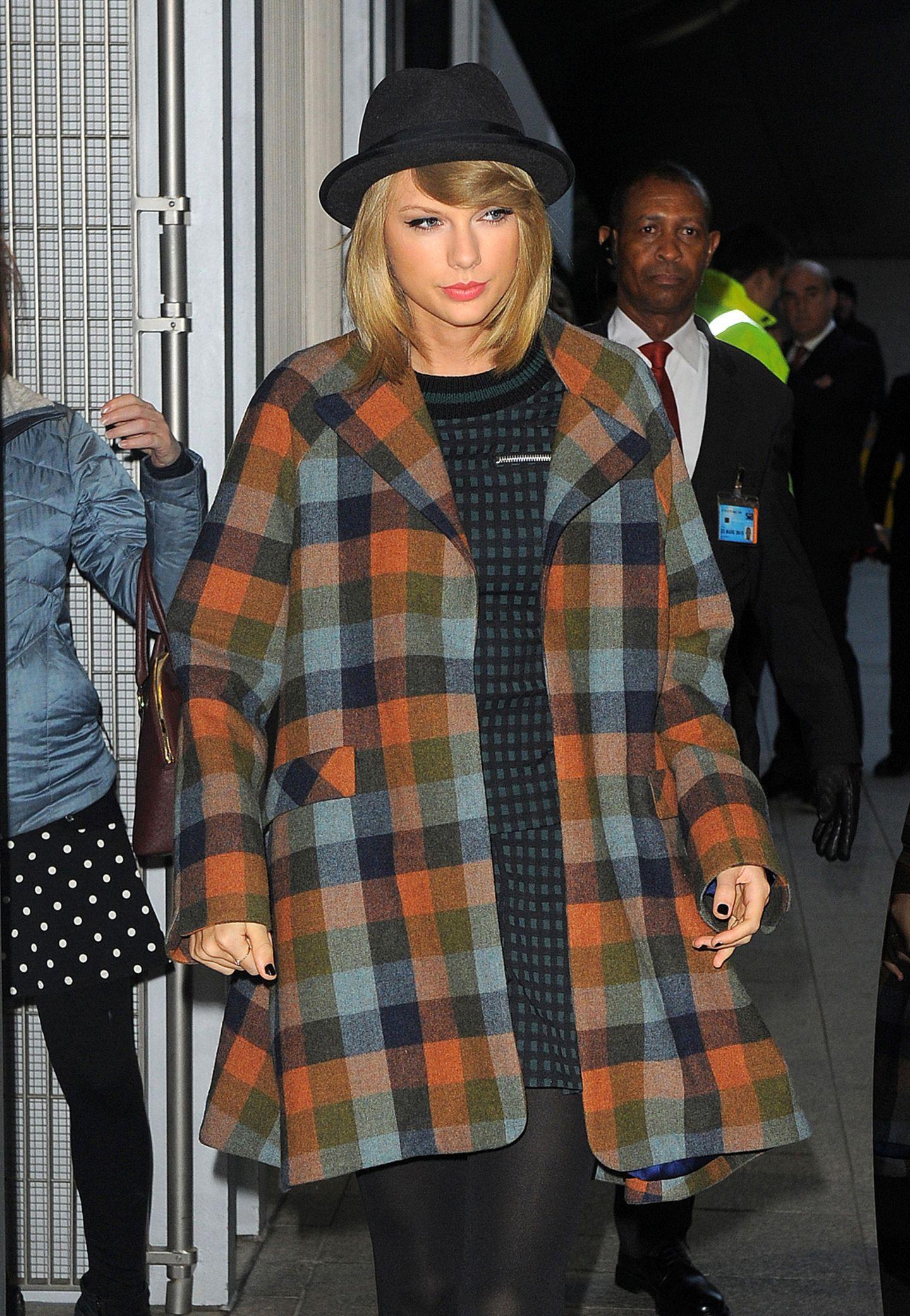 Taylor Swift scheut nicht vor verschiedenen Mustern bei diesem Outfit, denn zum Wollmantel im Holzfäller-Look kombiniert die Sängerin einen kleinkarierten Zweiteiler.