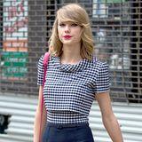 Das sehr klassische Karo-Muster ihres Etuikleides peppt Taylor Swift mit einer himbeerroten Schultertasche und türkisen Fingernägeln auf.
