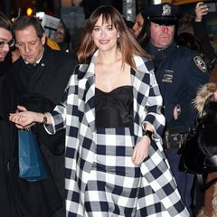 Dakota Johnson ist auf dem Weg zur Show von David Letterman und sieht dabei im großkarierten Ensemble aus Bleistiftrock und Retro-Mantel hinreißend aus.