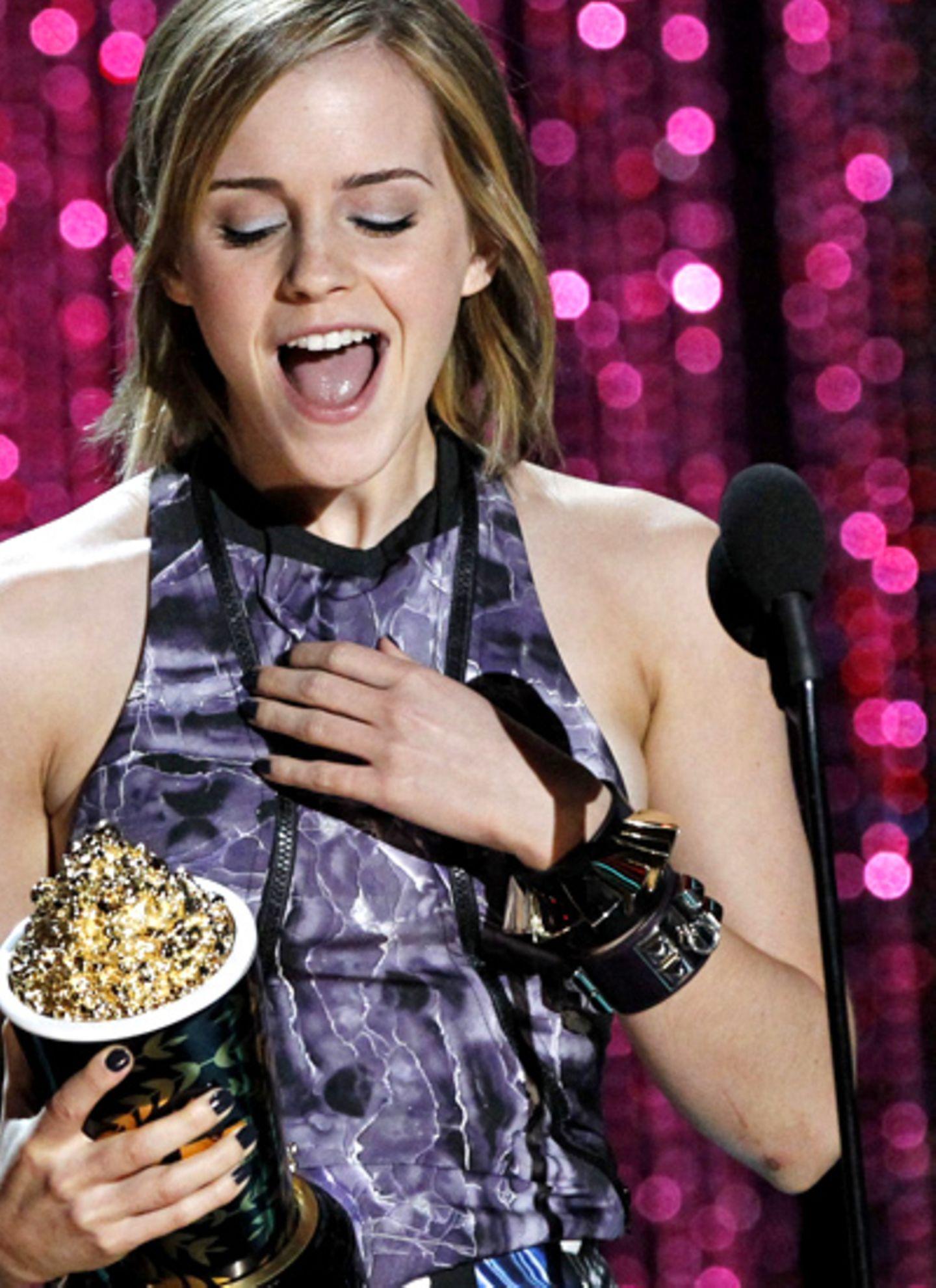 Emma Watson trägt zu den MTV Movie Awards gleich zwei wuchtige Armreifen, einer von Givenchy, der andere von Hermès.