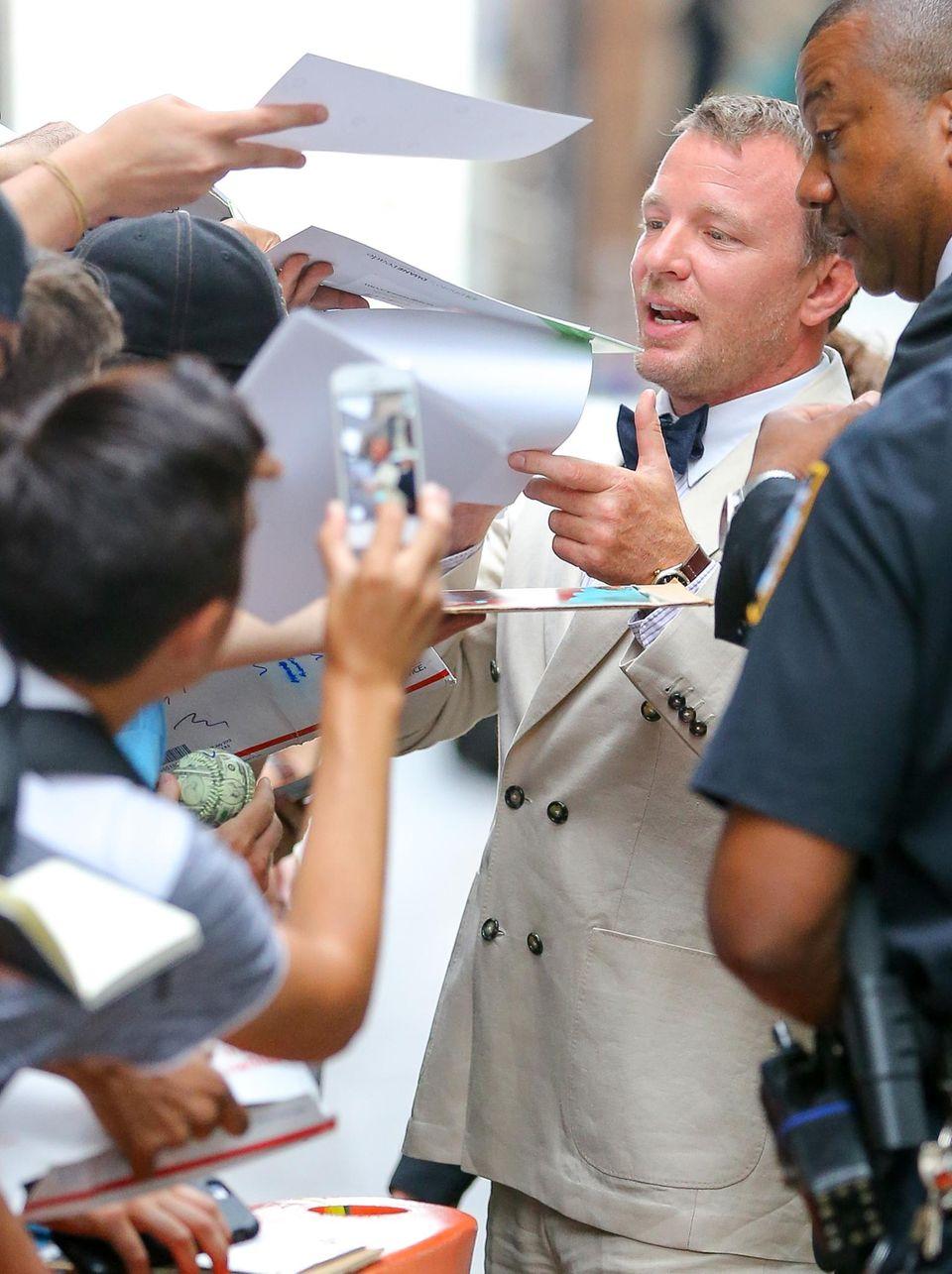 """Guy Ritchie stellt seinen Film """"Codename U.N.C.L.E."""" in New York vor und erfüllt den Fans Autogrammwünsche."""
