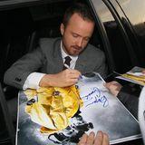 """""""Breaking Bad""""-Star Aaron Paul schreibt aus der Limousine heraus ein paar Autogramme."""