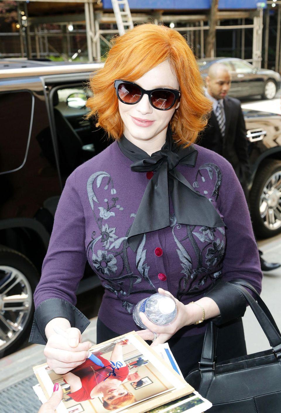 """Vor einem Talkshow-Auftritt in New York mit dem gesamten """"Mad Men""""-Cast schreibt Christina Hendricks Autogramme für die wartenden Fans."""