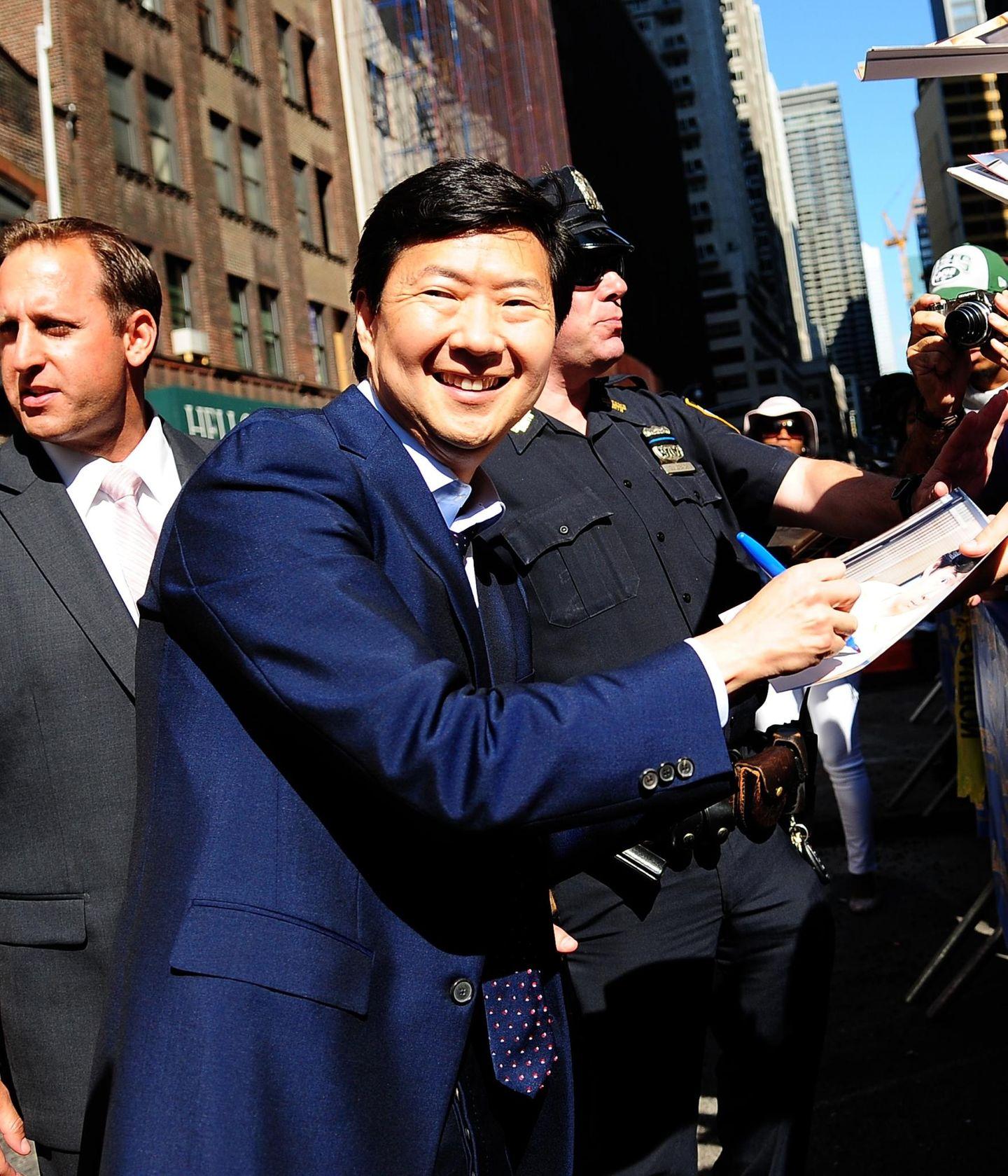 """Comedian Ken Jeong schreibt, nach seinem Besuch in der """"David Letterman Show"""", für seine Fans fleißig Autogramme."""