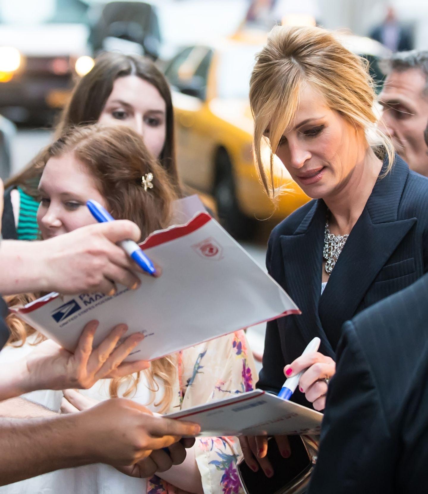 """Konzentriert schreibt Julia Roberts bei der """"The Normal Heart""""-Premiere in New York Autogramme."""