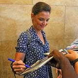 Ganz der Profi gibt Katie Holmes im Gehen ein paar Autogramme.