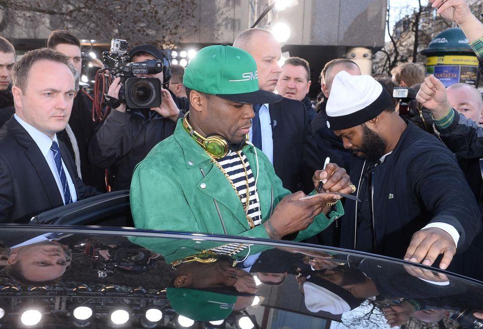 Bei seinem Besuch in Warschau schreit Rapper 50 Cent Autogramme für seine polnischen Fans.
