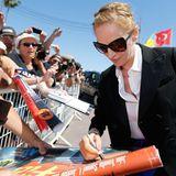 """Bei den Filmfestspielen in Cannes verteilt Uma Thurman Autogramme an ihre Fans. Einer hat extra sein """"Pulp Fiction""""-Filmplakat zum Signieren mitgebracht."""