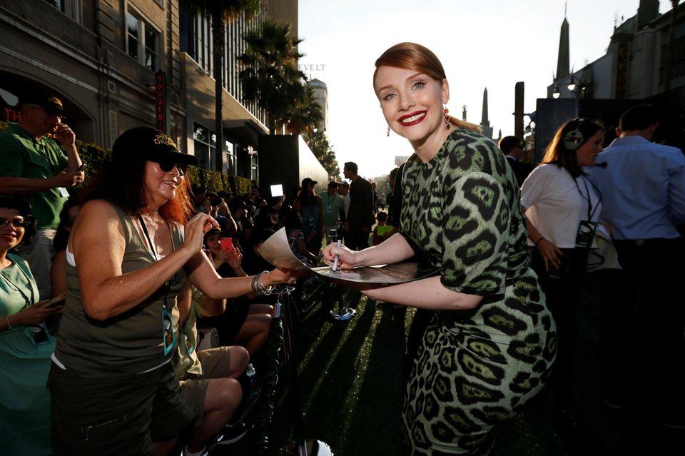 """Bei der Filmpremiere von """"Pete's Dragon"""" in Hollywood ist Schauspielerin Bryce Dallas Howard bester Laune und versucht alle Autogrammwünsche ihrer Fans zu berücksichtigen."""