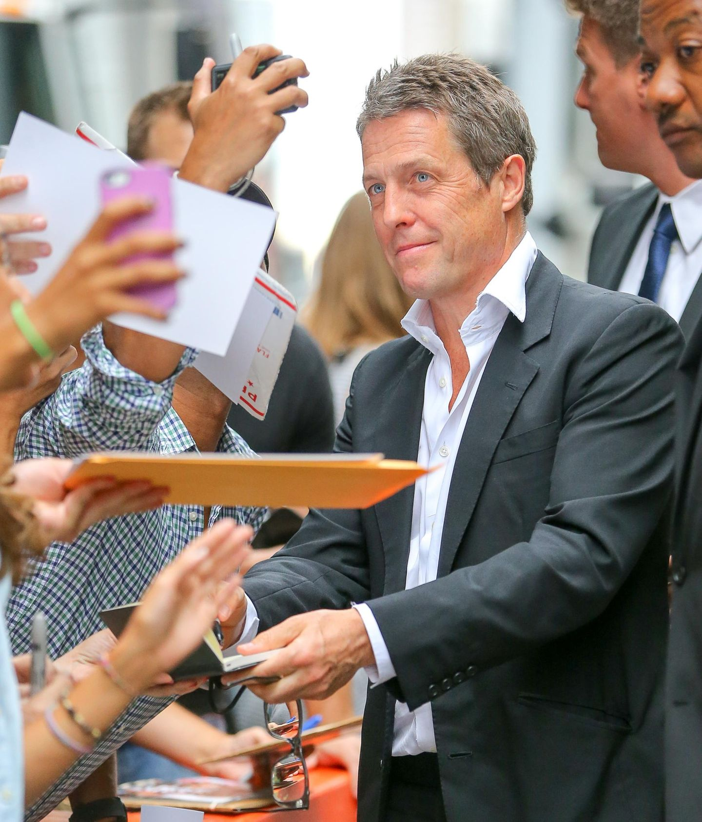 Hugh Grant schreibt vor dem Ziegfeld Theater in New York fleißig Autogramme.