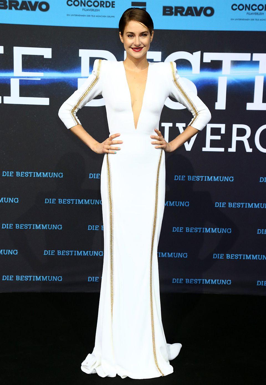 """Vor dem dunklen Hintergrund bei der Berliner Premiere von """"Divergent"""" leuchtet Shailene Woodley im weißen Zuhair-Murad-Kleid mit goldenen Reißverschluss-Details regelrecht. Der tiefe Ausschnitt wird da fast zur Nebensache."""