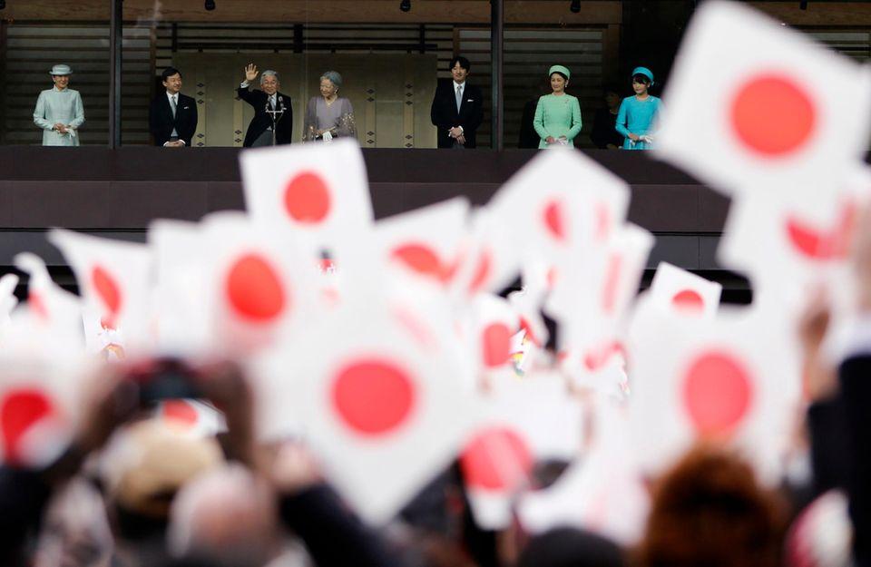 Japans Kaiser Akihito (3. v. l.) winkt seinem Volk, das sich zu Ehren seines 80. Geburtstages vor dem Palast in Tokio versammelt hat. Links von ihm posieren Kronprinzessin Masako und ihr Mann Naruhito, Akihitos Sohn, auf der rechten Seite des Balkons stehen Akihitos Frau Michiko, sein zweitgeborener Sohn Akishino, dessen Frau Kiko und die Tochter Mako.
