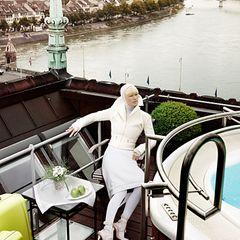 """Julia Gödicke blickt vom """"Grandhotel Les Trois Rois"""" und trägt eine weiße Kurzjacke mit Doppelkragen: Louis Vuitton, ca. 1.800 E"""