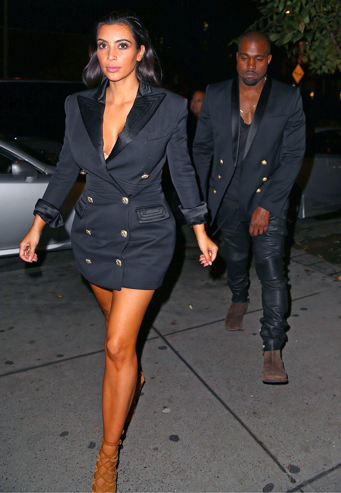 Modisch liegen Kim Kardashian und Eheman Kanye West voll auf einer Wellenlänge. Kim trägt ein Blazer-Kleid mit goldenen Knöpfen aus der Resort-Kollektion 2015 von Balmain, Kanye die passende Smoking-Jacke.