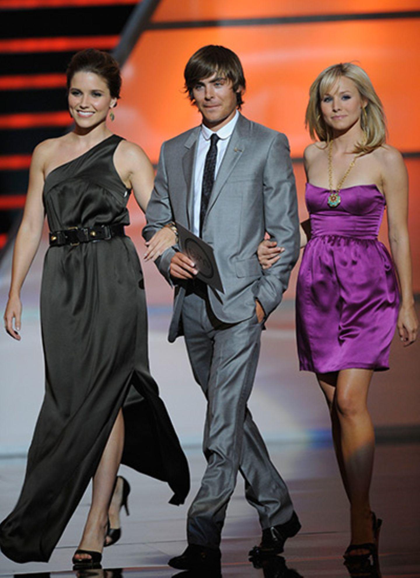 Hahn im Korb: Zac Efron betritt sichtlich stolz mit Sophia Bush und Kristen Bell die Bühne