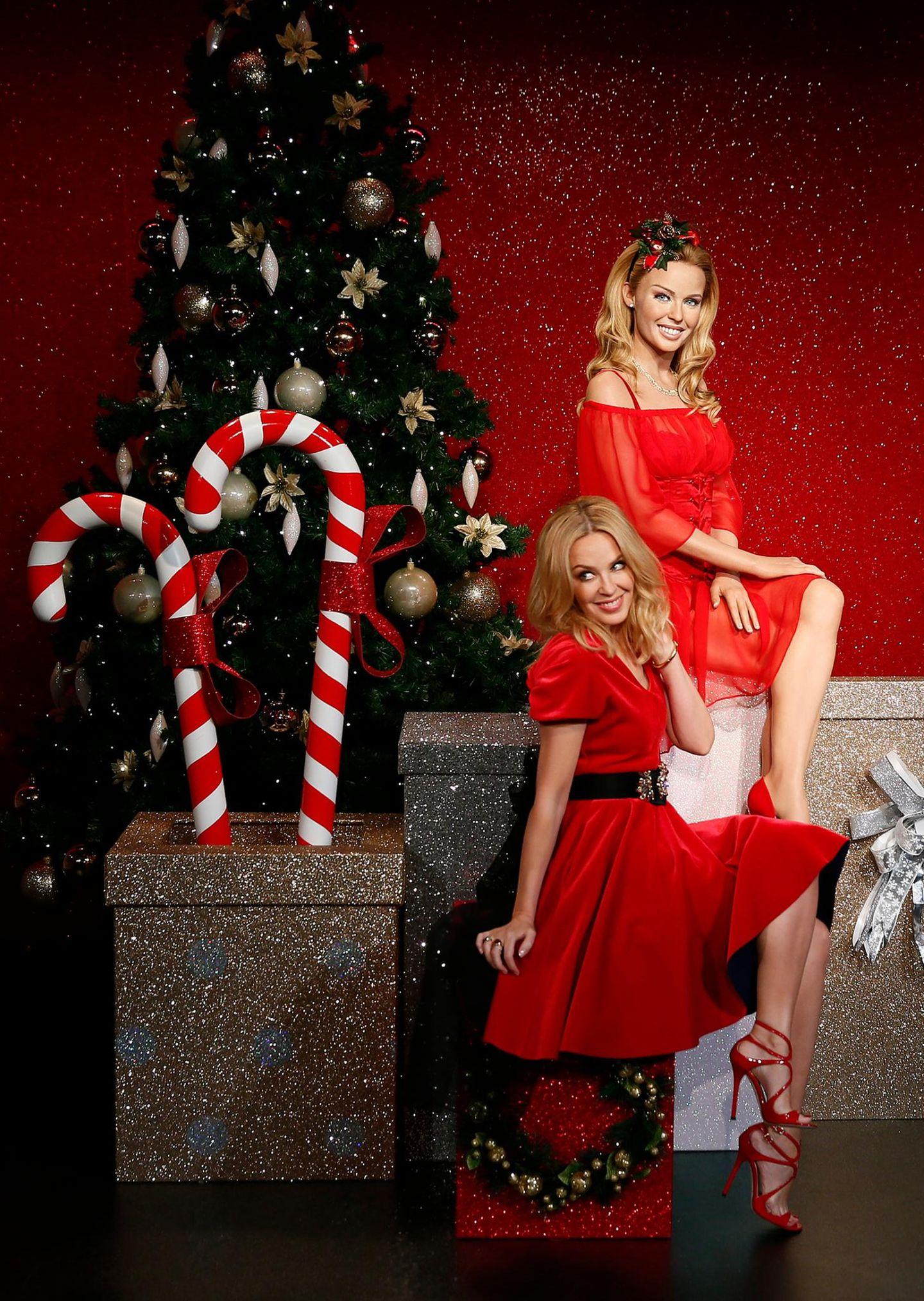 Eine Pose schöner als die andere: Bei Madame Tussauds in London macht Kylie Minogue es sich mit ihrem Wachsdouble vor'm Weihnachtsbaum gemütlich.