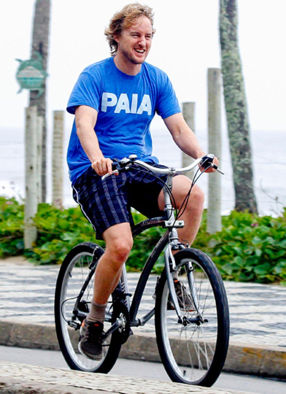 Bester Laune radelt Owen Wilson durch Rio de Janeiro und genießt dabei das schöne Wetter und die Landschaft.