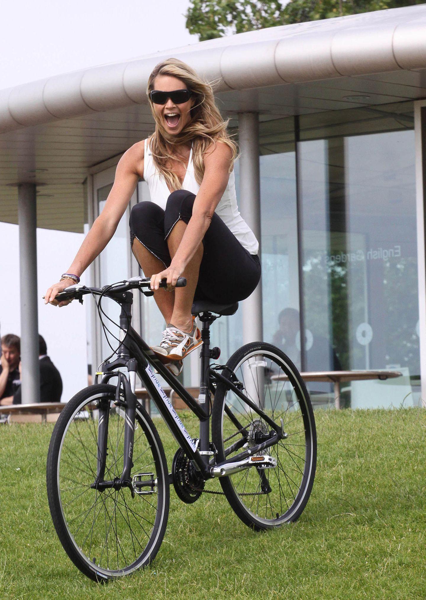 Elle Macpherson fährt schwungvoll auf ihrem Mountainbike bergab.