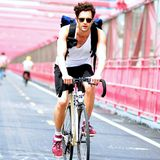 Penn Badgley radelt die Brooklyn Bridge entlang.