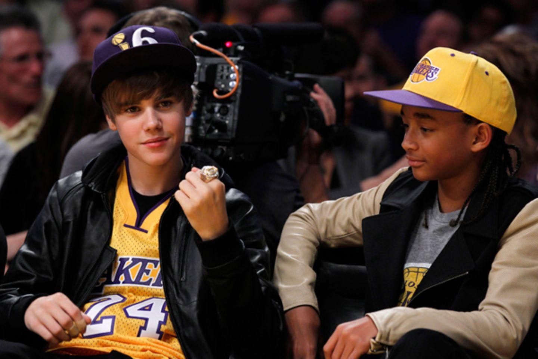 Justin Bieber ballt die Faust und bejubelt das Basketballteam der L.A. Lakers. Jaden Smith schaut auf den großen Ring am Finger