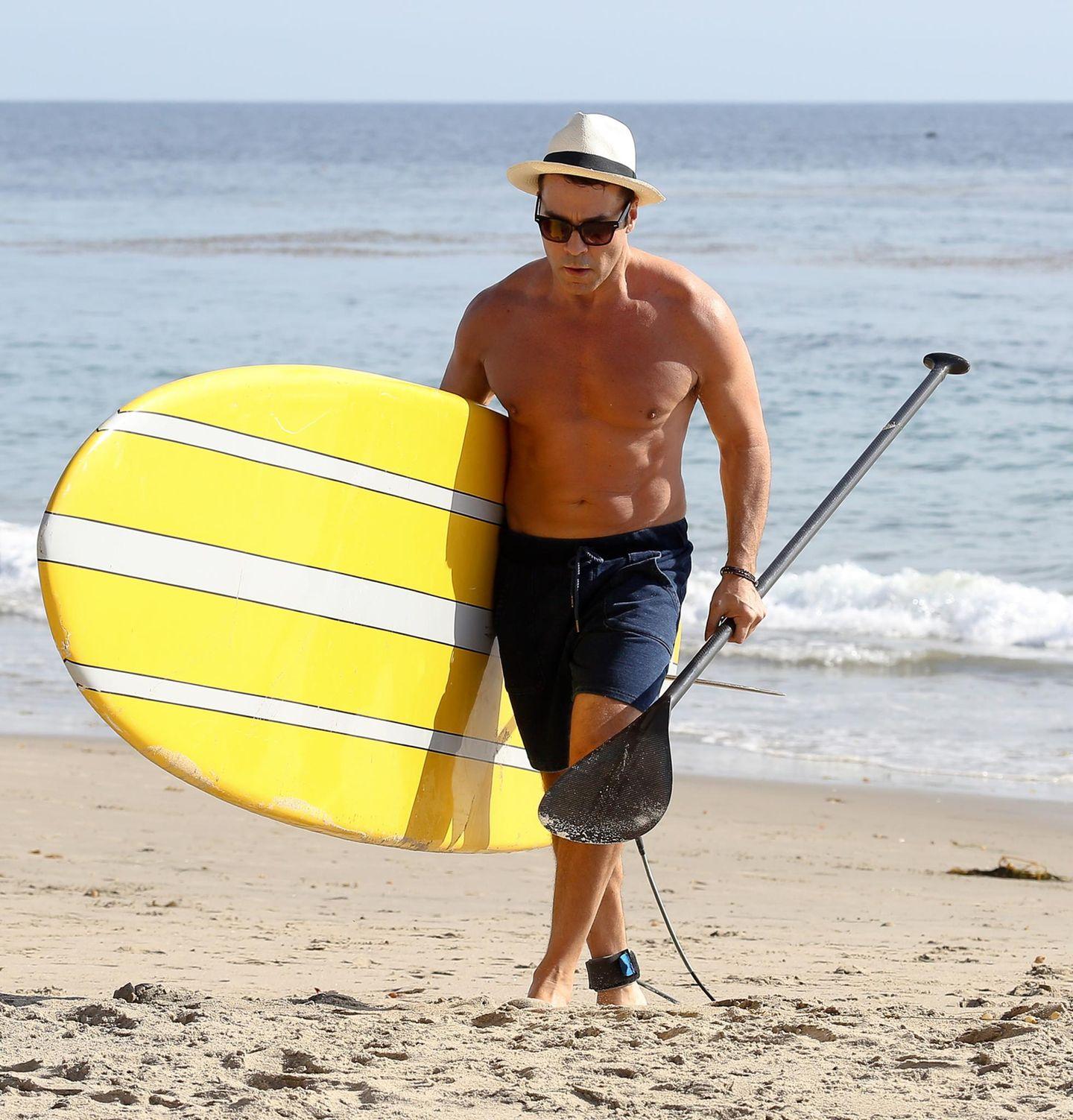 Jeremy Piven trägt sein Surfbrett enttäuscht zurück zum Strand, die Wellen sind heute in Los Angeles einfach zu niedrig.