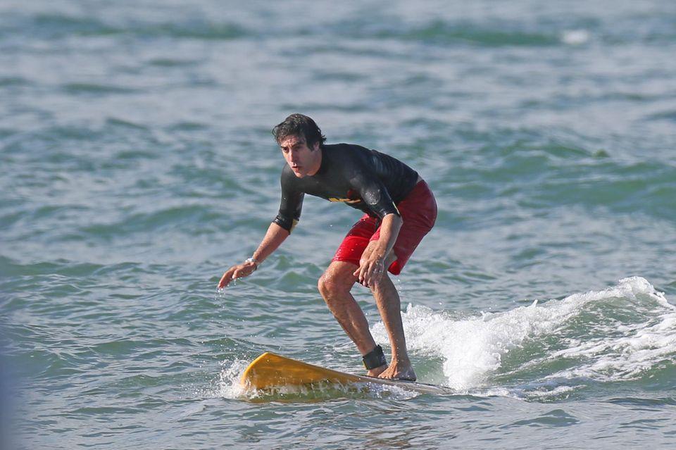 Sacha Baron Cohen versucht sich im Surfanzug auf Hawaii im Wellenreiten.