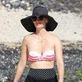 January Jones schlendert mit Sonnenhut und Sonnenbrille am Strand entlang. Besonders auffällig ist die Wahl ihres Bikinis und dem Polka-Dot-Badehöschen.