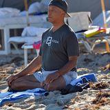 Russell Sommons enstpannt sich beim Yoga am Strand von Miami.