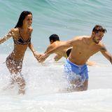 """Im Meer vor Rio de Janeiro sind der deutsche """"Paris St. Germain""""-Torwart Kevin Trapp und das """"Victoria's Secret""""-Model Izabel Goulart nicht nur auf Wolke 7, sondern auch auf Welle 7. Händchenhaltend stürzen sie sich ins Wasser und haben dabei sichtlich Spaß."""