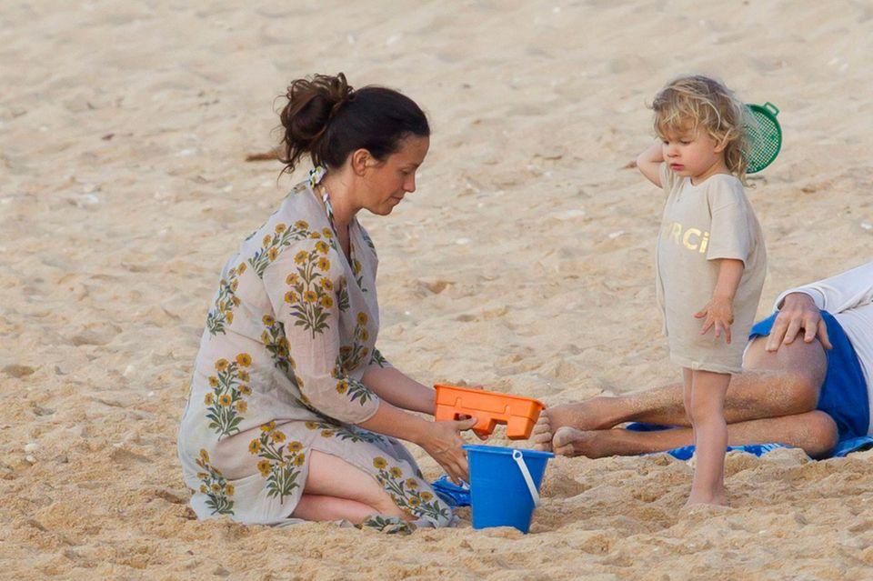 Alanis Morissette spielt mit Söhnchen Ever im Sand von Hawaii.