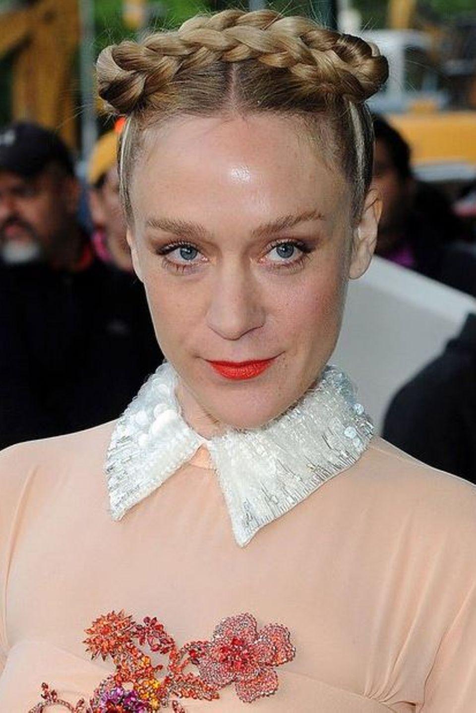 Stil-Ikone Chloë Sevigny trägt einen strengen Bauernzopf am Oberkopf geflochten und ergänzt damit ihr romantisches Kleid perfekt.