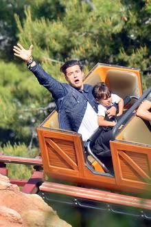 18. April 2015  Orlando Bloom hat sichtlich Spaß in der Achterbahn. Seinem Sohn Flynn scheint es in Disneyland weniger zu gefallen, er klammert sich ängstlich fest.