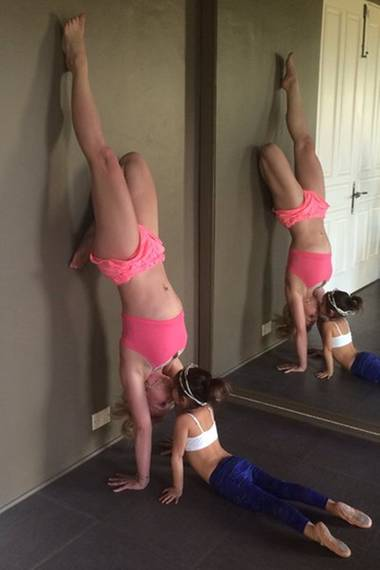 Gekonnt Balance halten: Britney Spears macht einen Yoga-Handstand und bekommt dabei noch ein Küsschen von einer kleinen Dame.