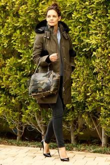 """Katie Holmes beweist auch bei niedrigen Temperaturen ihr tolles Stilgespür. Olivgrüner Parka, """"Rockstud""""-Shopper von Valentino, schwarze Jeans und spitze Lederpumps ergeben einen super Look."""