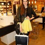 Mit einem fröhlichem Lächeln trägt Marie Nasemann ihre Alsterhaus-Tüte - Shoppen kann so viel Spaß bringen.
