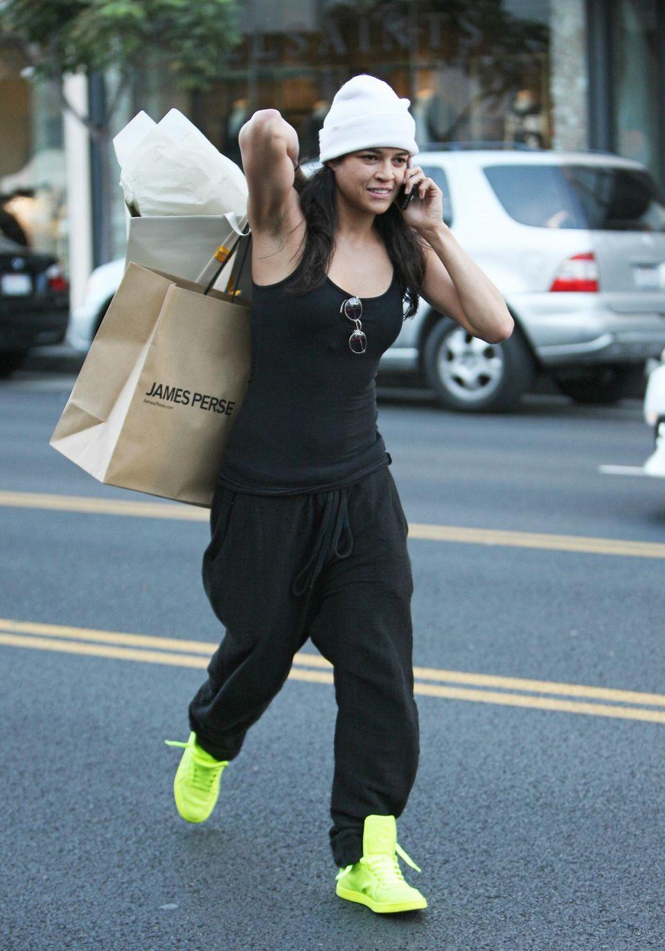 Multitasking: Während Michelle Rodriguez telefoniert, trägt sie ihre Einkaufstüten locker über die Schulter geworfen.