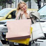 Vollbepackt mit diversen Einkaufstüten kommt Kate Hudson telefonierend vom Shopping.
