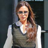 Victoria Beckham beweist, dass man auch an kühlen Tagen nicht auf eine luftige Bluse verzichten muss und trägt einen schicken Pullunder über ihrem Business-Look.