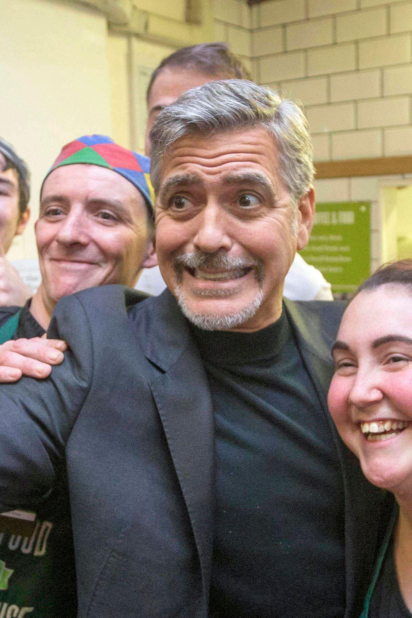 """Wer hat hier Existenzängste? Mit dieser Grimasse sorgt George Clooney im """"Social Bite"""", einem Obdachlosenheim in Edinburgh, für gute Laune. So ein Selfie hätte wohl jeder gern von ihm."""