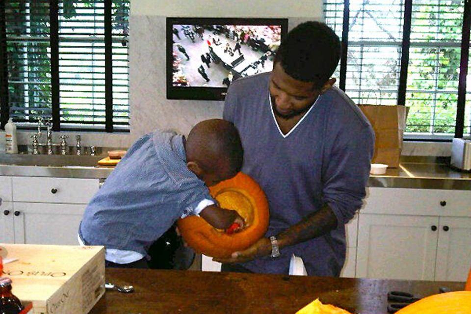 Usher und sein Sohn höhlen gemeinsam einen Riesenkürbis aus.