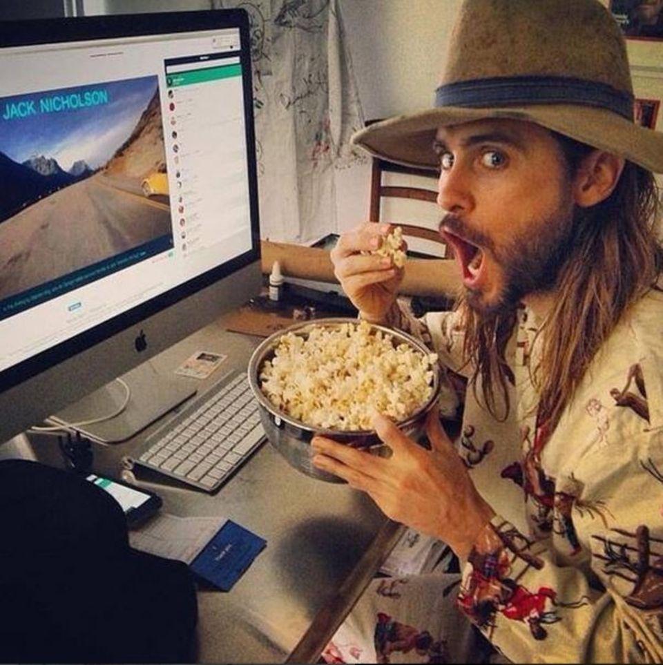 """Jared Leto mag's gern ungewöhnlich: im schrägen Pyjama und dem Film """"Shining"""" lässt er sich eine Schüssel Popcorn schmecken."""