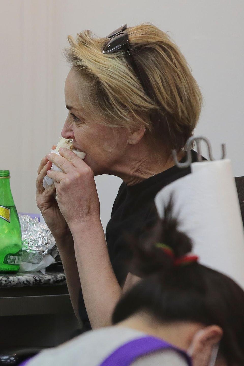 Während sich Sharon Stone ihre Nägel lackieren lässt, isst sie genüsslich ihren Wrap.