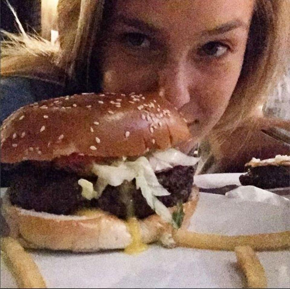 Bar Refaeli genießt mit allen Sinnen und riecht erst einmal am Burger bevor sie hineinbeißt.