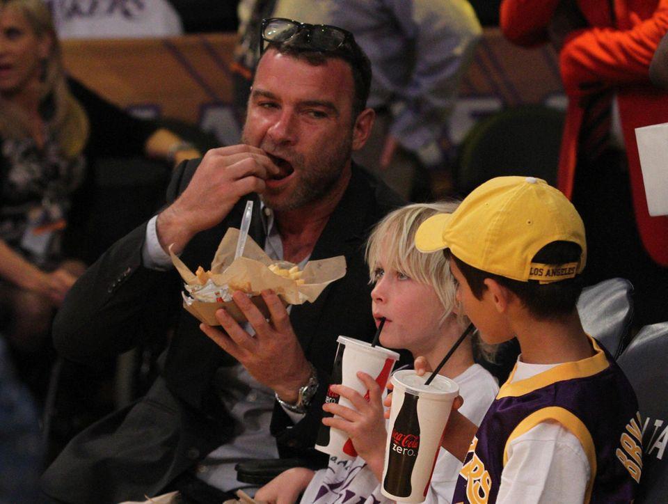 """Pommes und Cola gehören einfach zu einem """"Lakers"""" Spiel dazu. In Los Angeles genießen Liev Schreiber mit Sohnemann Alexander und einem Freund das Basketballspiel."""
