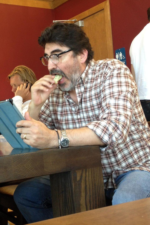 Alfred Molina lässt sich einen Muffin schmecken, während er Nachrichten auf seinem Tablet liest.