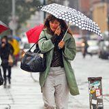 Helena Christensen läuft telefonierend und mit Pünktchenschirm durch das regnerische New York.