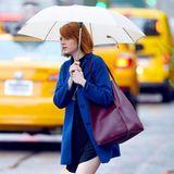 Emma Stone holt mit Schirm und Mantel ausgerüstet Kaffe für sich und einen Freund.