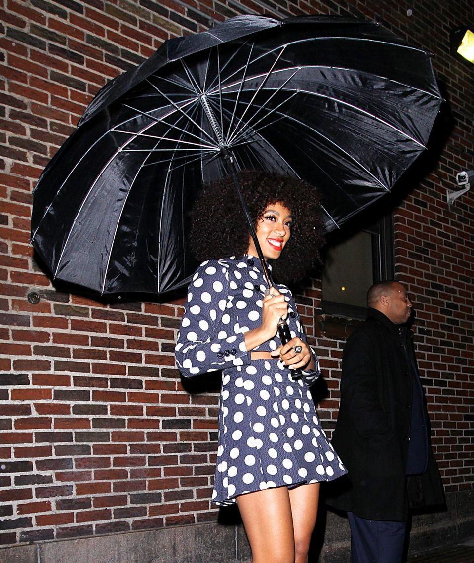 Troz Regen strahlt Solange Knowles unter ihrem XXL-Regenschrim.